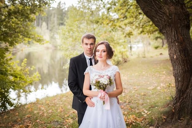 Bruid en bruidegom omarmen in herfst park