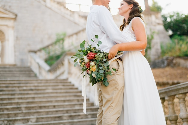Bruid en bruidegom omarmen op de oude klokkentoren in de buurt van de kerk in prcanj bruid bedrijf bruiloft Premium Foto