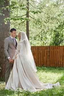 Bruid en bruidegom omarmen prachtige bruiloft in de natuur