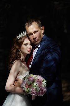 Bruid en bruidegom omhelzen en kussen in het donkere bos in de zon. bruiloft in de natuur, portret van een verliefd stel in het park