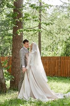 Bruid en bruidegom omhelzen, mooie bruiloft in de natuur. liefdevol jong stel