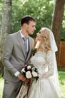 Bruid en bruidegom omhelzen, mooie bruiloft in de natuur. liefdevolle jong koppel