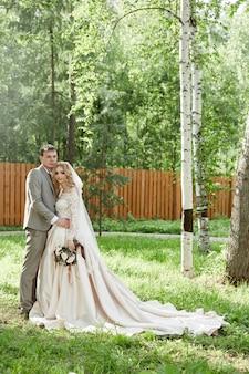 Bruid en bruidegom omhelzen, mooie bruiloft in de natuur. liefdevolle jong koppel Premium Foto