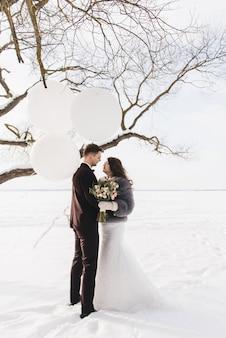 Bruid en bruidegom onder besneeuwde landschap met grote witte ballonnen