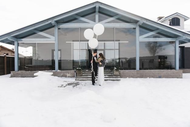 Bruid en bruidegom onder besneeuwde landschap met witte grote ballonnen