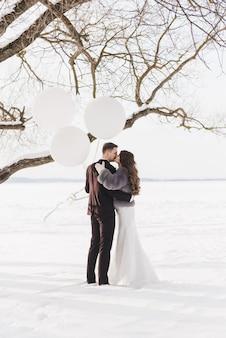 Bruid en bruidegom onder het besneeuwde landschap.