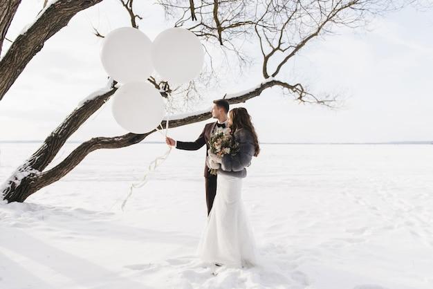 Bruid en bruidegom onder sneeuwlandschap met grote witte ballonnen