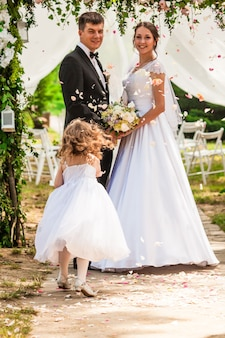 Bruid en bruidegom op de huwelijksceremonie. schattig meisje overlaadde de pasgetrouwden met vliegende rozenblaadjes