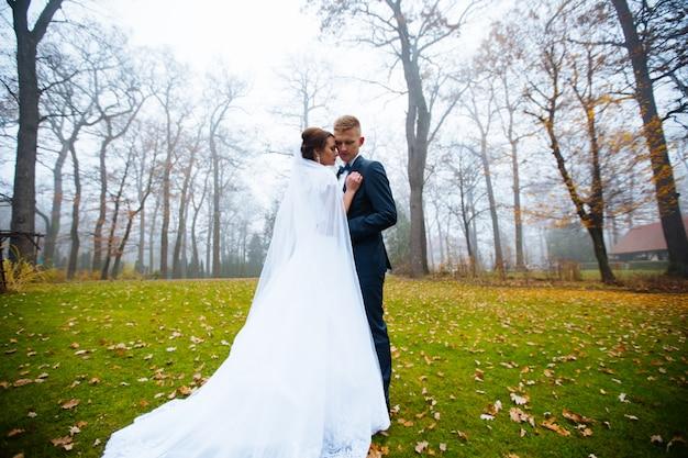 Bruid en bruidegom op huwelijksdag buiten lopen in het voorjaar de natuur. bruidspaar, gelukkig pasgetrouwde vrouw en man omarmen in herfst park. liefdevolle bruidspaar buiten. bruid en bruidegom