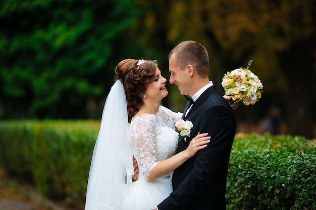 Bruid en bruidegom op huwelijksdag buiten lopen op herfst natuur. bruidspaar, gelukkig jonggehuwde vrouw en man omarmen in groen park. liefdevolle bruidspaar buiten.