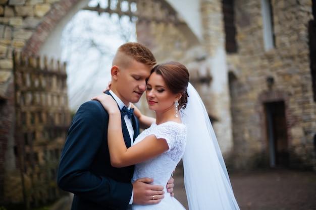 Bruid en bruidegom op huwelijksdag buiten lopen op lente aard. bruidspaar, gelukkig jonggehuwde vrouw en man omarmen in groen park. liefdevolle bruidspaar buiten.