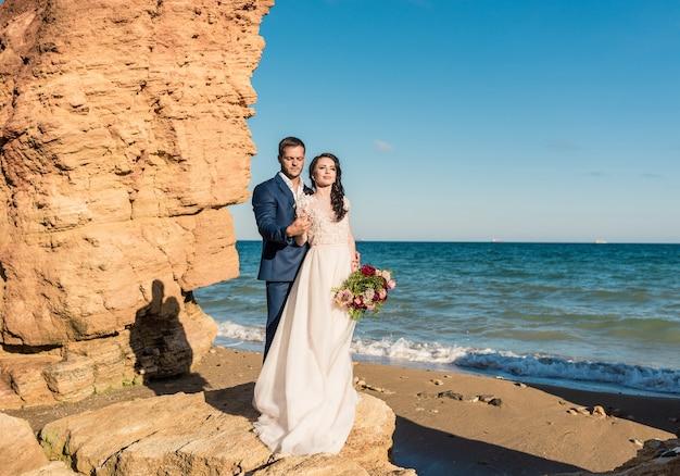 Bruid en bruidegom op huwelijksdag op het strand in de buurt van de zee. glimlachende bruid en bruidegom. jong paar verliefd.