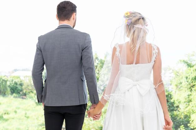 Bruid en bruidegom paar van kaukasische glimlach en hand in hand samen.