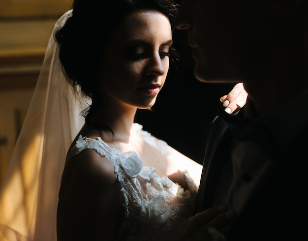 Bruid en bruidegom poseren in de slecht verlichte kamer