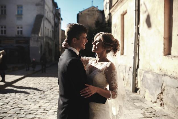 Bruid en bruidegom poseren in de straten van de oude stad
