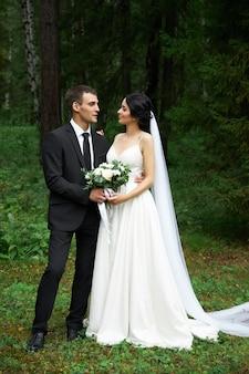 Bruid en bruidegom poseren in een bos