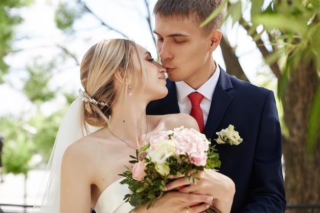 Bruid en bruidegom poseren in een park