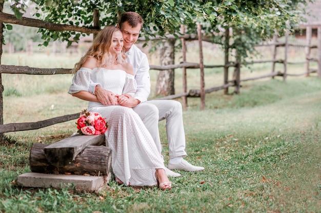 Bruid en bruidegom poseren op een bankje