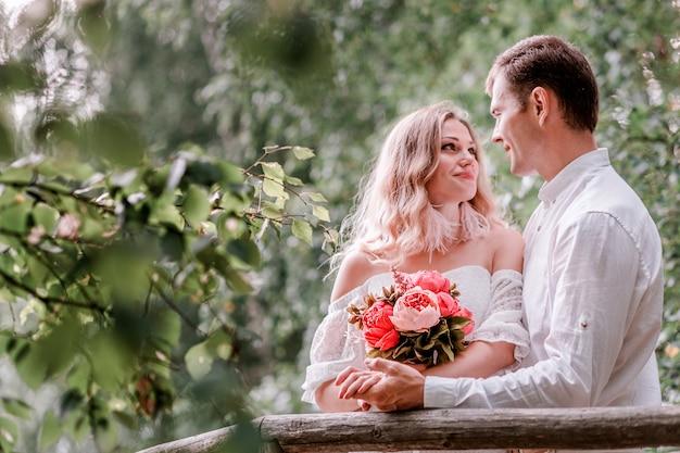 Bruid en bruidegom poseren op een brug
