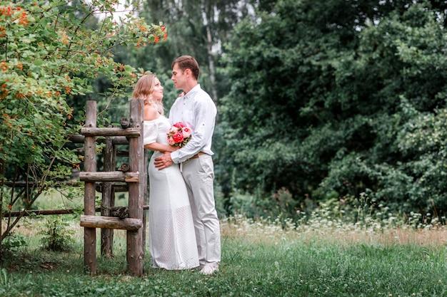 Bruid en bruidegom poseren op een veld met groen gras