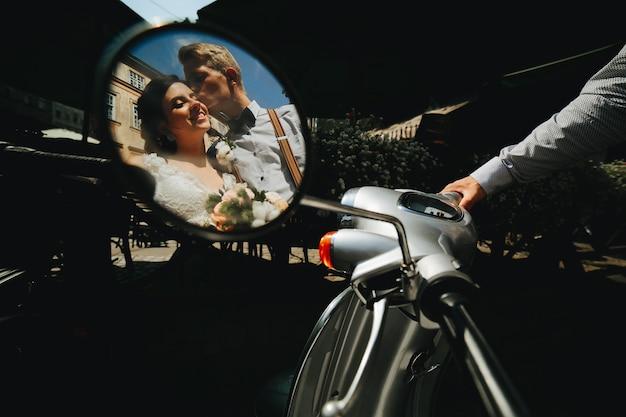 Bruid en bruidegom poseren op een vintage motorscooter