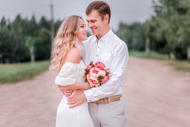 Bruid en bruidegom poseren op een weg