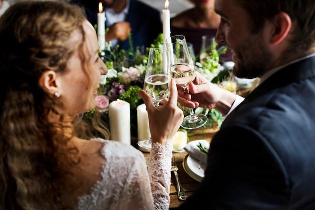 Bruid en bruidegom roosteren met wijnglazen op een bruiloft receptie