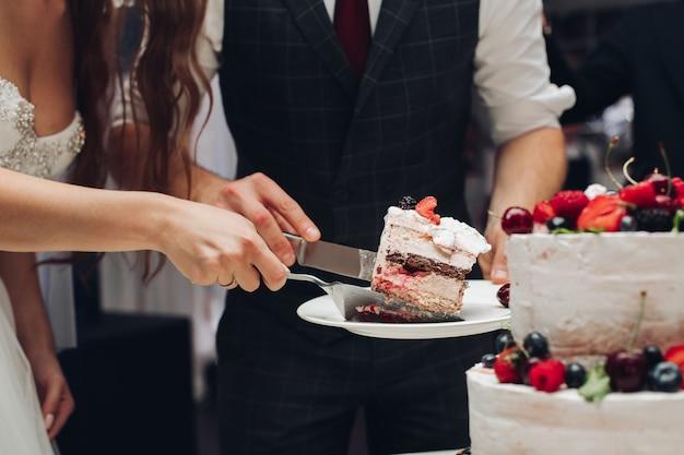 Bruid en bruidegom snijden bruidstaart stuk van lekker zoet dessert. concept van zoetwaren, feest en liefde.