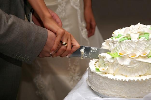 Bruid en bruidegom snijden de bruidstaart close-up