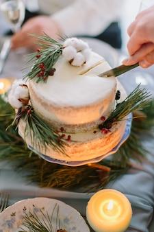 Bruid en bruidegom snijden de bruidstaart versierd met dennen, bessen en katoen bloem