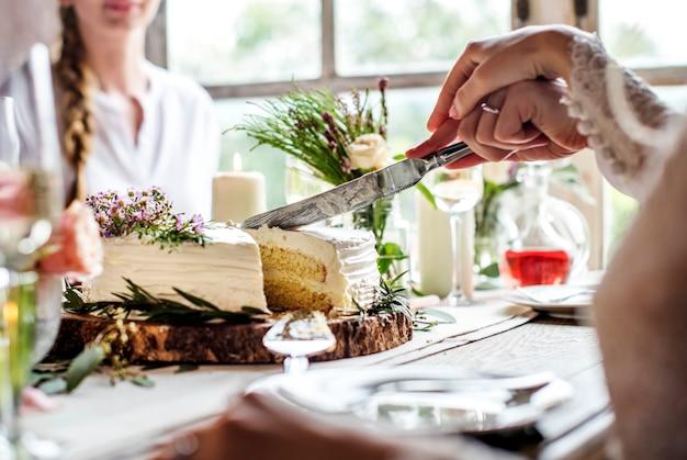 Bruid en bruidegom snijden taart op bruiloft receptie