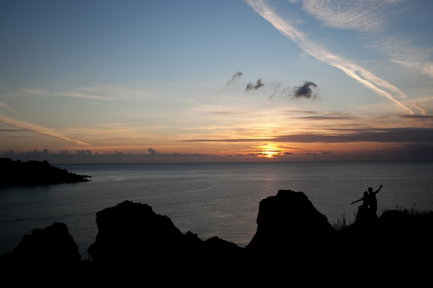 Bruid en bruidegom spreidden hun handen uit tijdens het kijken naar de zonsondergang
