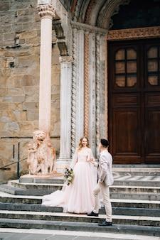Bruid en bruidegom staan hand in hand op de trap bij de ingang van de basiliek van santa maria