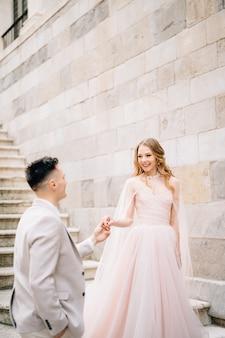 Bruid en bruidegom staan hand in hand op de trappen van een oud gebouw in bergamo, italië