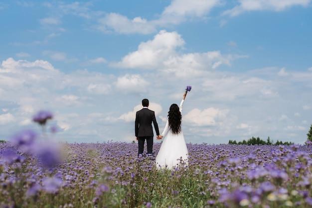 Bruid en bruidegom staan in een veld met bloemen in de zomer op de huwelijksdag