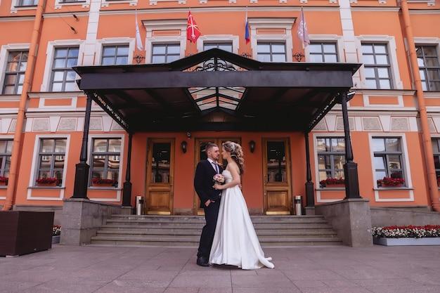 Bruid en bruidegom staan om de hoofdingang van het gebouw met een oude gevel. pasgetrouwden in trouwjurken op zonnige trouwdag. koppel op straat in een prachtig uitzicht. jonggehuwden verliefd samen gelukkig
