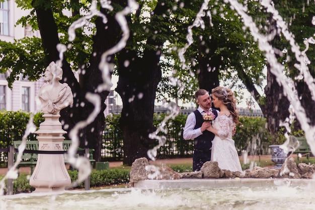 Bruid en bruidegom staan omarmen in park achter fontein met stromend water. pasgetrouwden in trouwjurken op zonnige trouwdag. koppel op straat in een prachtig uitzicht. jonggehuwden verliefd samen gelukkig