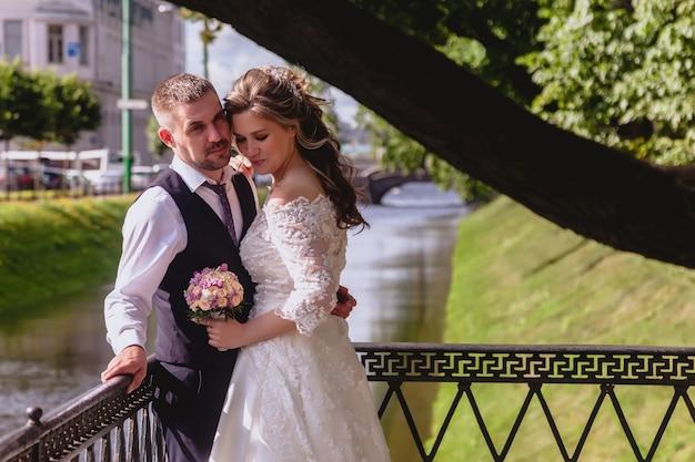 Bruid en bruidegom staan omarmen in park met rivierkanaal op de achtergrond. pasgetrouwden in trouwjurken op zonnige trouwdag. koppel op straat in een prachtig uitzicht. jonggehuwden verliefd samen gelukkig