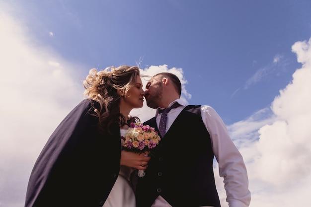 Bruid en bruidegom staan omarmen op blauwe hemelachtergrond met wolken. pasgetrouwden in trouwjurken op zonnige trouwdag. koppel op de natuur in een prachtig uitzicht. jonggehuwden verliefd samen gelukkig
