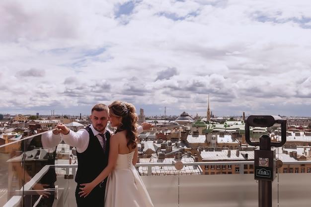 Bruid en bruidegom staan omarmen op het dak met panoramisch uitzicht over de oude stad. pasgetrouwden in trouwjurken op zonnige trouwdag. koppel op dak in geweldig uitzicht. jonggehuwden verliefd op de achtergrond van de stad