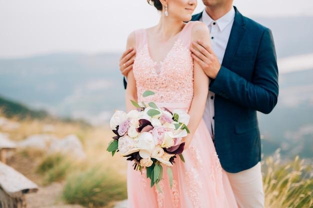 Bruid en bruidegom staan op de berg: de bruidegom knuffelt zachtjes de bruid van achteren.