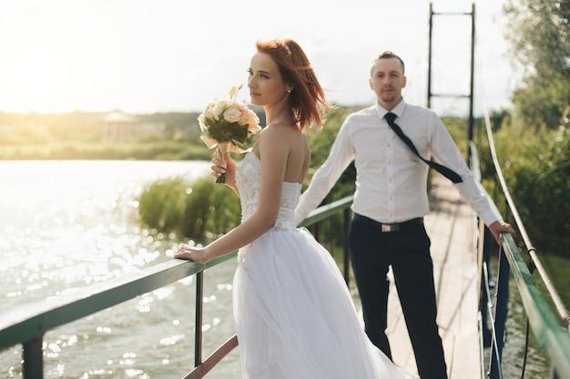 Bruid en bruidegom staan op de brug