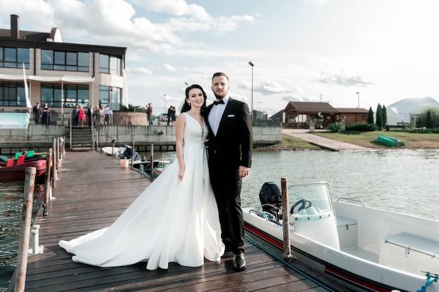 Bruid en bruidegom staan op de pier