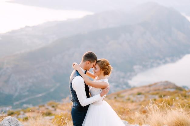 Bruid en bruidegom staan op de top van de berg lovcen met uitzicht op de baai van kotor en omhelzen elkaar teder