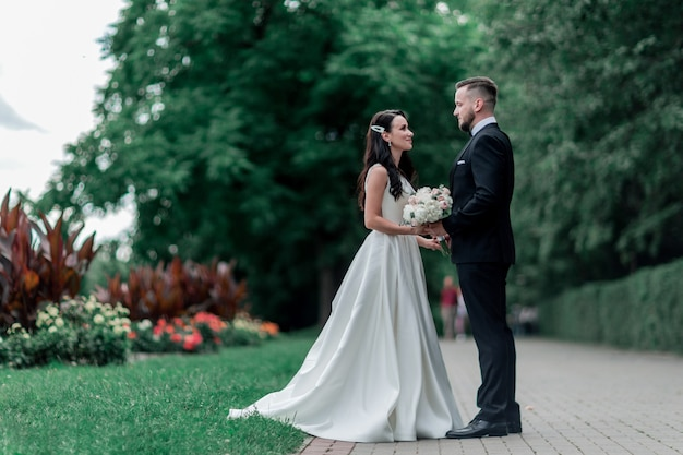 Bruid en bruidegom staan op het pad in het stadspark. vakanties en evenementen
