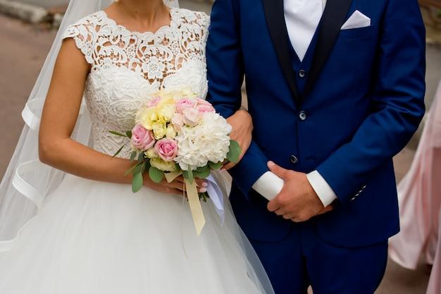 Bruid en bruidegom staan samen met hun handen.