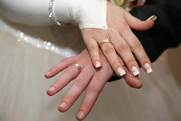 Bruid en bruidegom tonen hun handen met trouwringen