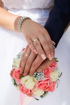 Bruid en bruidegom tonen hun trouwringen op de achtergrond van het boeket