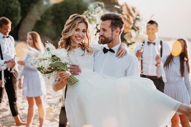 Bruid en bruidegom trouwen met gasten op een strand
