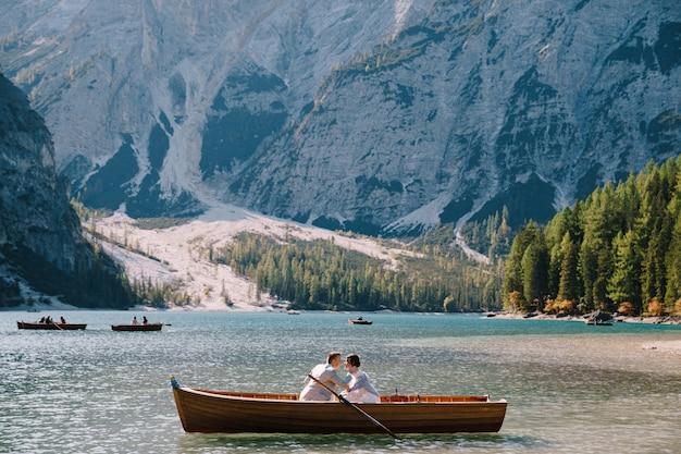 Bruid en bruidegom varen in een houten boot aan het lago di braies in italië. trouwen in europa, op het meer van braies
